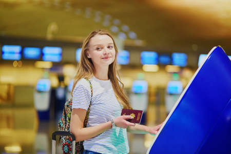 Young woman in international airport doing self check-in