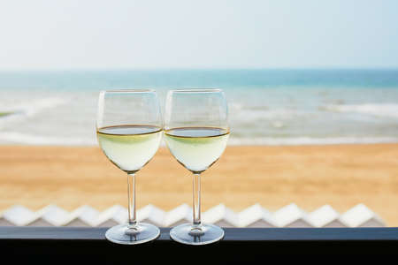 Two glasses of white wine with Atlantic coast beach in background. Normandy, France Stock Photo