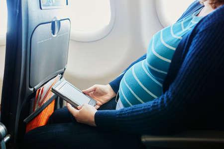 Mujer embarazada en el segundo trimestre que viaja en avión. Madre para ir de vacaciones o viaje de negocios. ¿Es seguro viajar durante el embarazo?