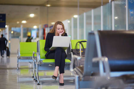 Young woman in international airport working on laptop while waiting for her flight Фото со стока