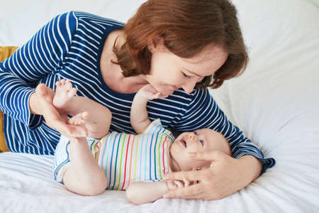 Mother and child in nursery. Mom and baby girl in bedroom. Parent and infant having time together and relaxing at home Stock Photo - 103895175