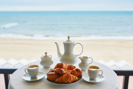 Two cups of coffee and traditional French pastry in cafe or restaraunt with a view. Breakfast on balcony near sea or ocean