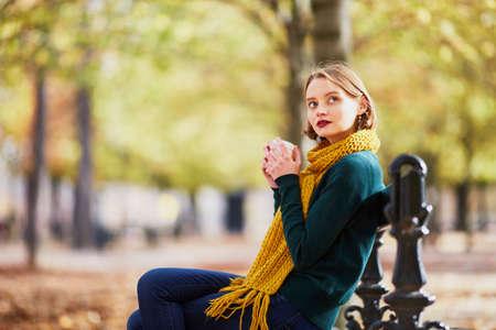 Heureuse jeune fille en écharpe jaune avec du café pour aller se promener dans le parc d'automne par une belle journée d'automne