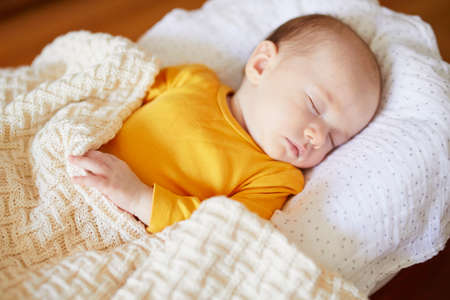 Adorable baby girl sleeping under knitted blanket in nursery