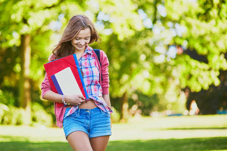 Cheerful young student with books and folders at campus on a sunny summer or fall day. Back to school concept