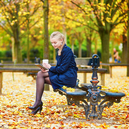 Beautiful young woman in the Luxembourg garden of Paris on a fall day, drinking coffee to go Stockfoto