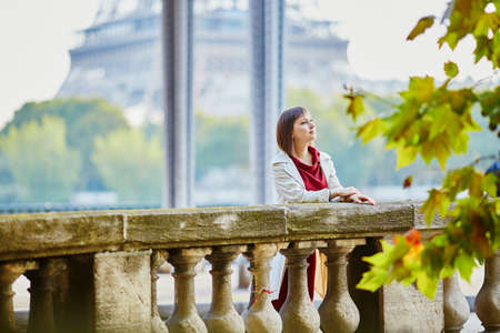 Beautiful young woman in Paris on Bir-Hakeim bridge with view to Eiffel tower on a fall or spring day. Tourism and vacation in France 스톡 콘텐츠