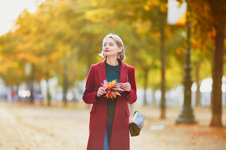 Schöne junge Frau mit Bündel bunte Herbstblätter, die im Park an einem Herbsttag gehen