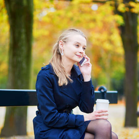 Beautiful young woman drinking coffee and speaking on the phone in the Luxembourg garden of Paris on a fall day Foto de archivo