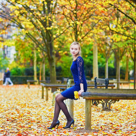 Beautiful young woman in blue dress in the Luxembourg garden of Paris on a fall day