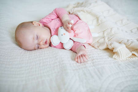 Baby girl having a nap with her favorite mouse toy. Little child sleeping on bed with comforter. Infant kid in sunny nursery