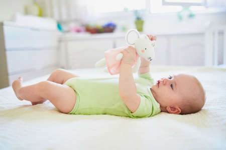 Baby girl playing with her favorite toy. Little child lying on bed with comforter. Infant kid in sunny nursery Stock fotó