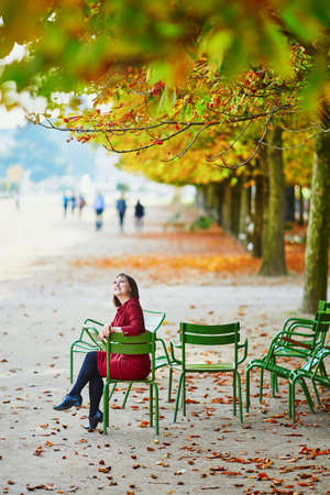 Beautiful young woman in Tuileries garden of Paris on a bright fall day. Tourism and vacation in France at autumn season Stock Photo