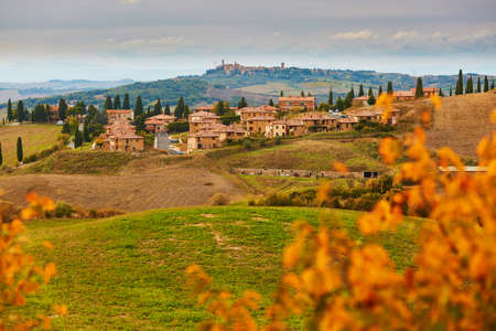 Scenic Tuscan landscape with small village on top of hill. San Quirico dOrcia, Tuscany, Italy