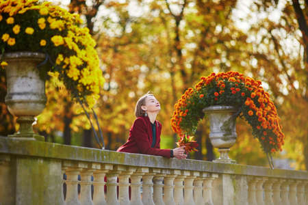 Beautiful young woman with bunch of colorful autumn leaves walking in park on a fall day. Luxembourg garden, Paris, France