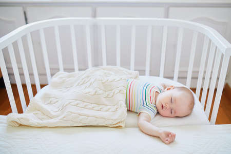 Adorable baby girl sleeping in co-sleeper crib attached to parents bed. Little child having a day nap in cot. Infant kid in sunny nursery Stock Photo