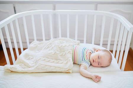 Entzückendes kleines Mädchen, das im Co-Sleeper-Kinderbett am Elternbett schläft. Kleines Kind, das ein Tagesschläfchen im Kinderbett hat. Kleinkind im sonnigen Kinderzimmer Standard-Bild