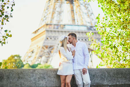Happy couple near the Eiffel tower. Tourists enjoying their vacation in France. Romantic date or traveling couple concept