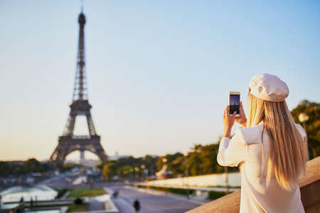 Young woman with long blond hair taking photo of the Eiffel tower in Paris, Fance