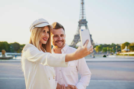 Happy couple taking selfie near the Eiffel tower. Tourists enjoying their vacation in France. Romantic date or traveling couple concept 写真素材 - 107003820