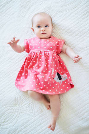 Six months old baby girl in pink dress. Little child in bright clothes lying on bed in nursery. Fashion for infants