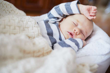 Adorable baby girl sleeping in the crib. Little child having a day nap in cot. Infant kid resting in nursery