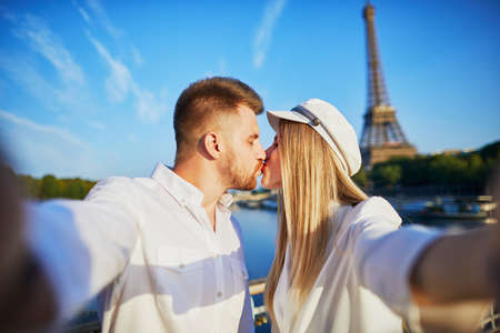 Happy couple taking selfie near the Eiffel tower. Tourists enjoying their vacation in France. Romantic date or traveling couple concept