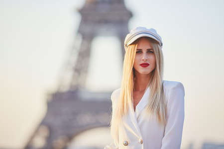 Pretty young woman with long blond hair and red lips posing in front of the Eiffel tower in Paris, Fance