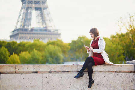 Beautiful young woman in Paris near the Eiffel tower and the Seine on a bright fall day, using mobile phone for texting, browsing or photo. Tourism and vacation in France at autumn season Stock Photo