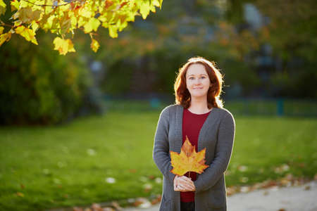 Beautiful woman in autumn clothes outdoors in park on a bright sunny fall day Stock Photo
