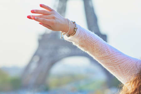 Happy young woman near the Eiffel tower in Paris, France. Tourist showing her bracelet with mini Eiffel tower