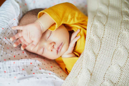 Adorable newborn baby girl sleeping in bed at home