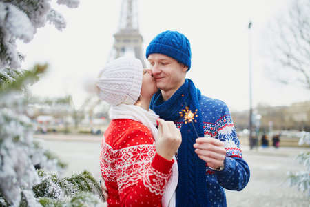 Happy couple near Christmas tree under snow with the Eiffel tower in the background on a winter day. Trip to Paris during season holidays Stock Photo
