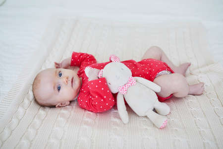 Baby girl lying on bed with toy. Little child playing in sunny nursery