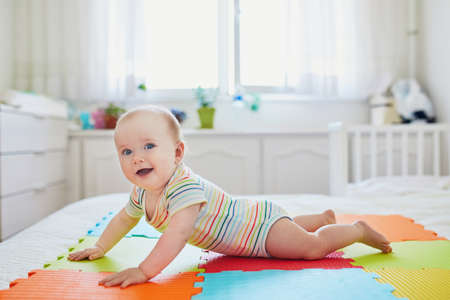 Baby girl learning to crawl. Little child lifting her body on arms. Infant kid in sunny nursery Stock Photo