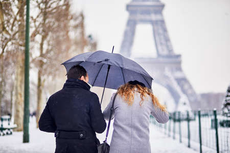 Couple of tourists walking in Paris under umbrella on a day with heavy snow. Unusual weather conditions in Paris 写真素材 - 109760334