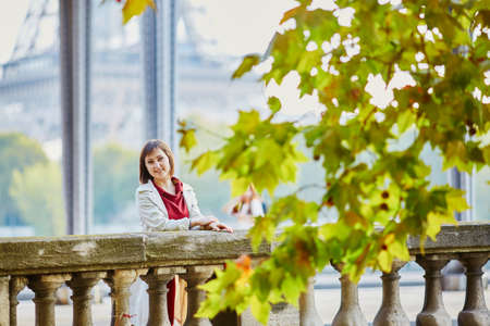 Beautiful young woman in Paris on Bir-Hakeim bridge with view to Eiffel tower on a fall or spring day. Tourism and vacation in France Stock Photo