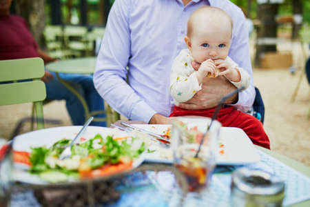 Father holding his daughter on lap while eating in restaurant. Baby trying solids. Baby led weaning concept