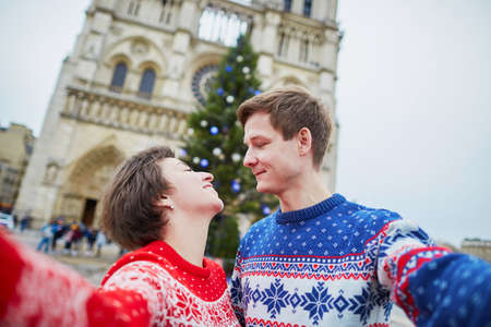 Happy couple in colorful sweaters taking selfie with mobile phone near Notre-Dame cathedral and decorated Christmas tree in Paris, France 写真素材 - 108222503