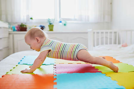 Baby girl learning to crawl. Little child lifting her body on arms. Infant kid in sunny nursery Stok Fotoğraf