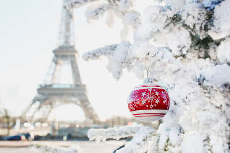 Christmas tree covered with snow and decorated with red ball on a street of Paris, France. Eiffel tower in the background. Trip to France during holidays season concept