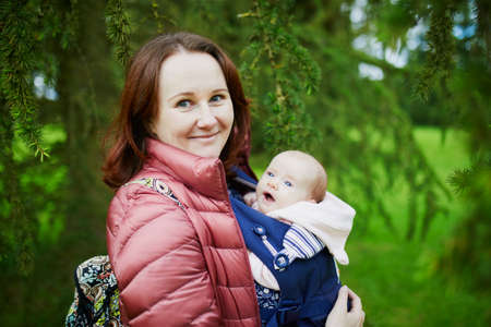 Young mother with her little daughter in carrier. Woman walking with baby girl. Outdoor activities for families Stock Photo - 108222608