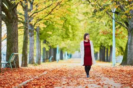Beautiful young woman in Paris walking in park on a bright fall day. Tourism and vacation in France at autumn season