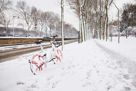 Bike for rent on a Parisian street on a day with heavy snow. Winter snowfall in Paris, France