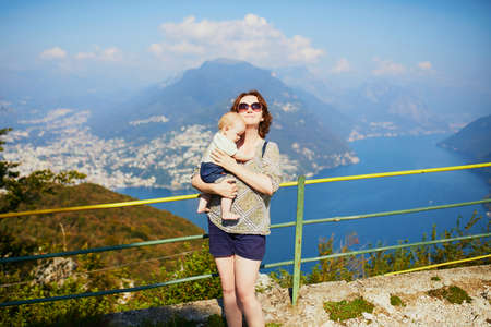 Woman with little girl enjoying scenic view to the lake Lugano from mountain San Salvatore in Lugano, canton of Ticino, Switzerland. Mother with baby on a view point. Travelling with kids 스톡 콘텐츠