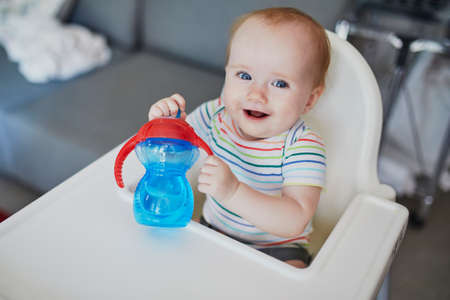 Little baby girl sitting in high chair at home or at restaurant and drinking water from sippy cup