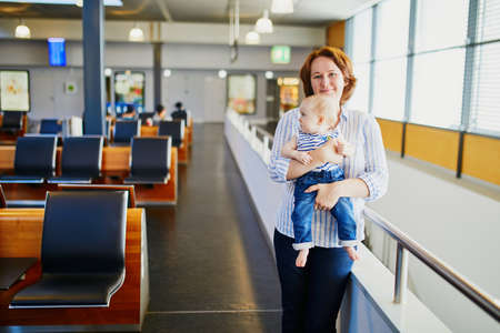 Woman with little girl in international airport. Mother with baby waiting for their flight. Travelling with kids