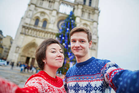 Happy couple in colorful sweaters taking selfie with mobile phone near Notre-Dame cathedral and decorated Christmas tree in Paris, France 写真素材 - 109611162