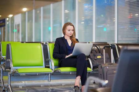 Jonge vrouw in internationale luchthaven die op laptop werkt tijdens het wachten op haar vlucht