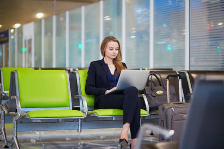Young woman in international airport working on laptop while waiting for her flight Banco de Imagens